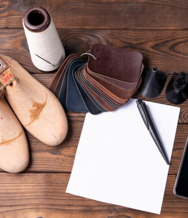 leather-samples-shoes-wooden-shoe-last-dark-wooden-table-with-empty-white-sheet-paper-notes-designer-furniture-clothes-shoe-maker-workspace
